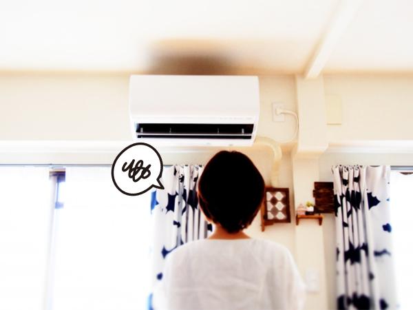 エアコンを見上げて買い替えようか悩んでいる女性